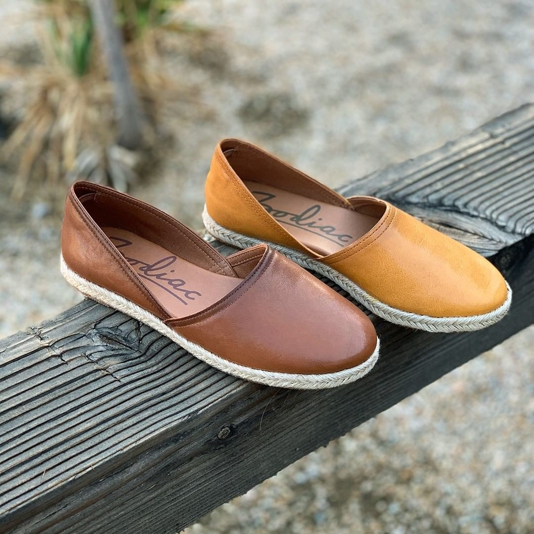 Two espadrille flats in dark brown and mustard with a braided outsole sitting on a piece of wood