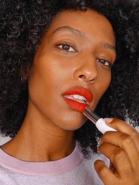 Model applies light red Glossier Sheer Matte Lipstick to their lips