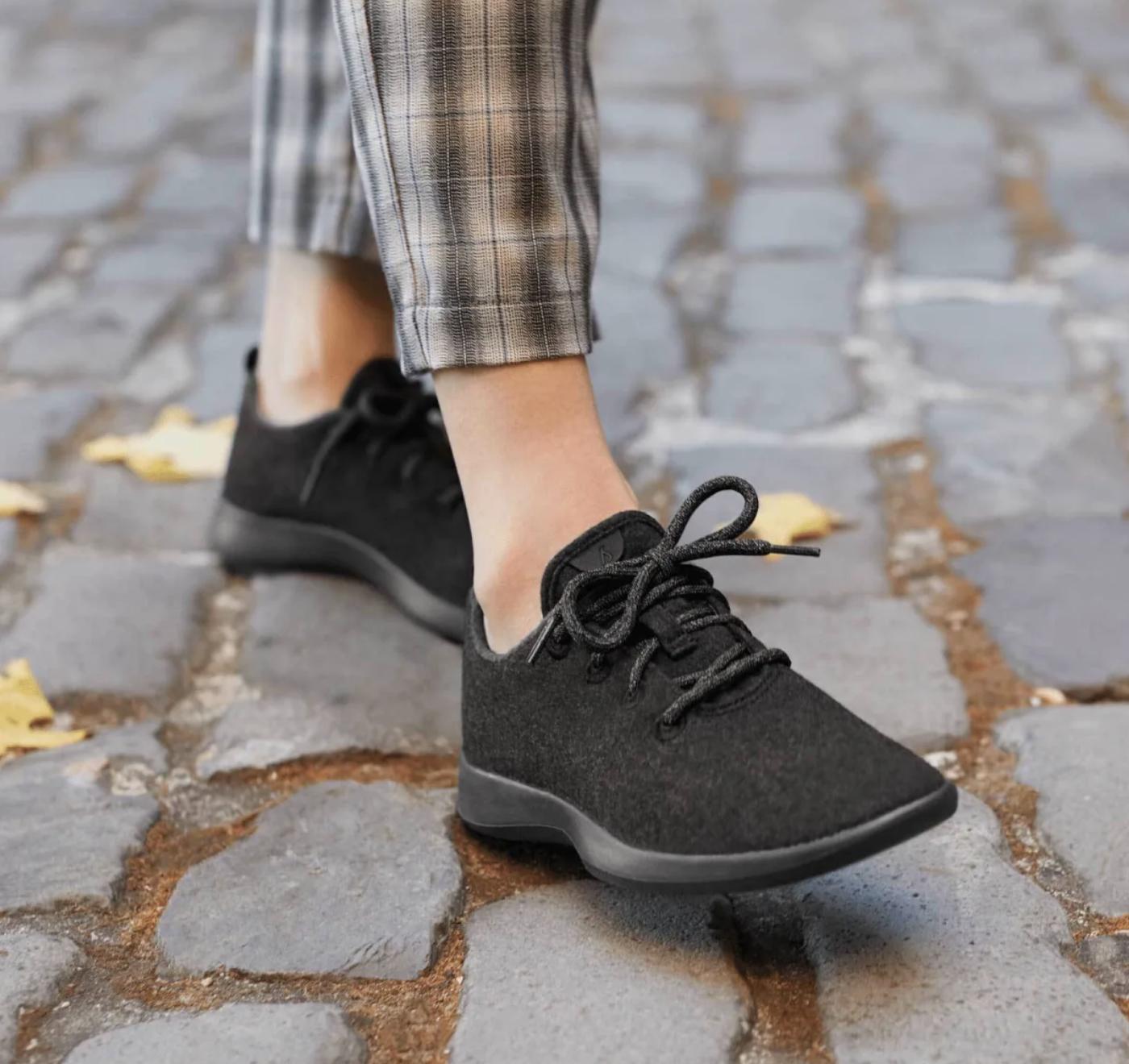 model in all black Allbirds wool sneakers