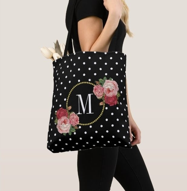 Model carrying a monogramed tote bag with polkadots and flowers on it