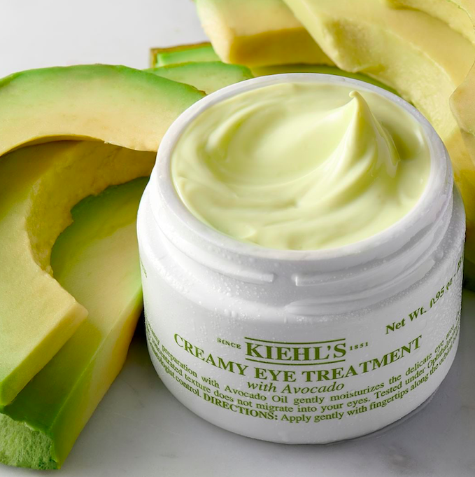 "White container that says ""Kiehl's Creamy Eye Treatment with Avocado"" next to chopped up avocado slices"