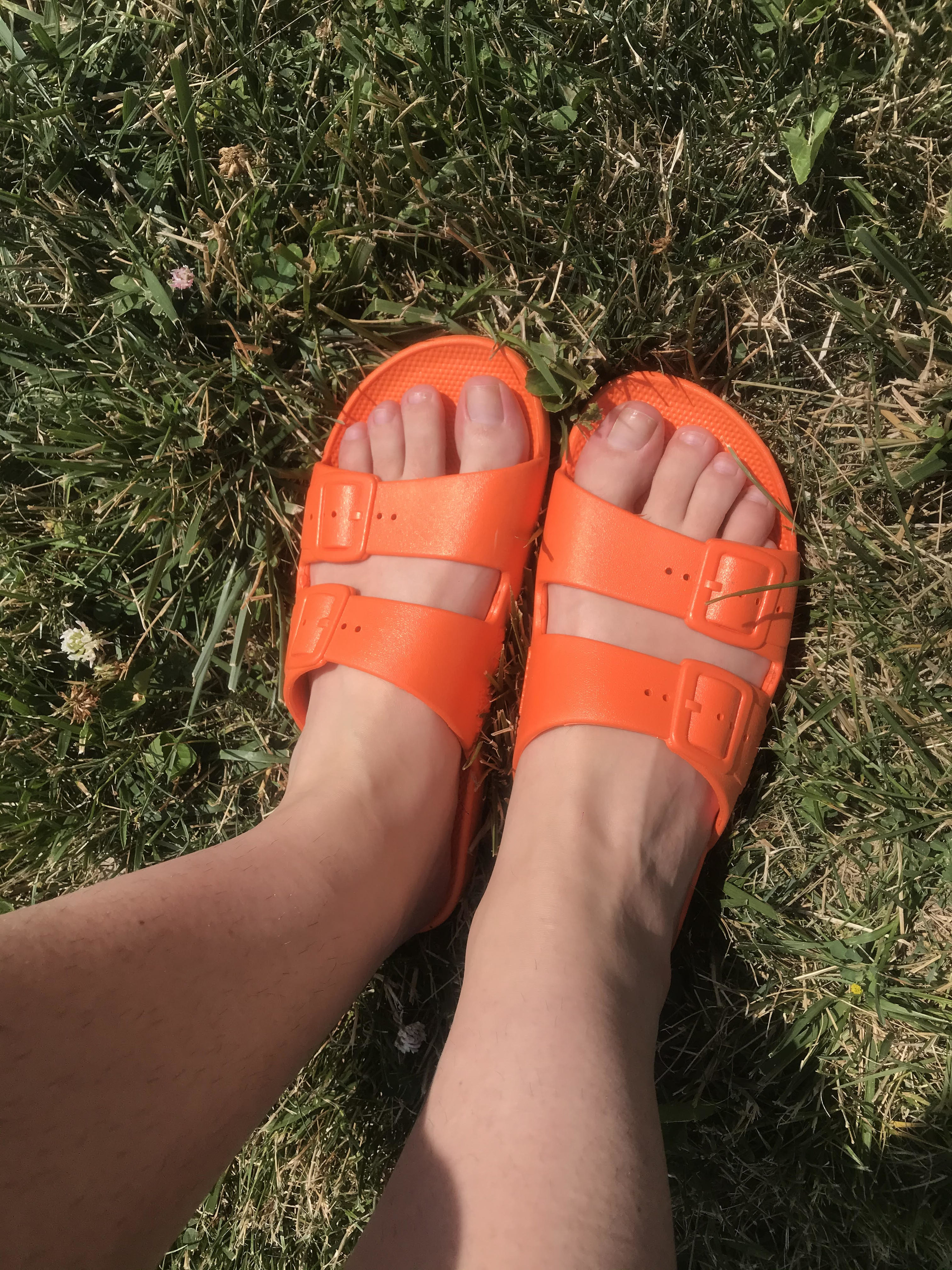 writer's feet in orange slides with two buckled straps