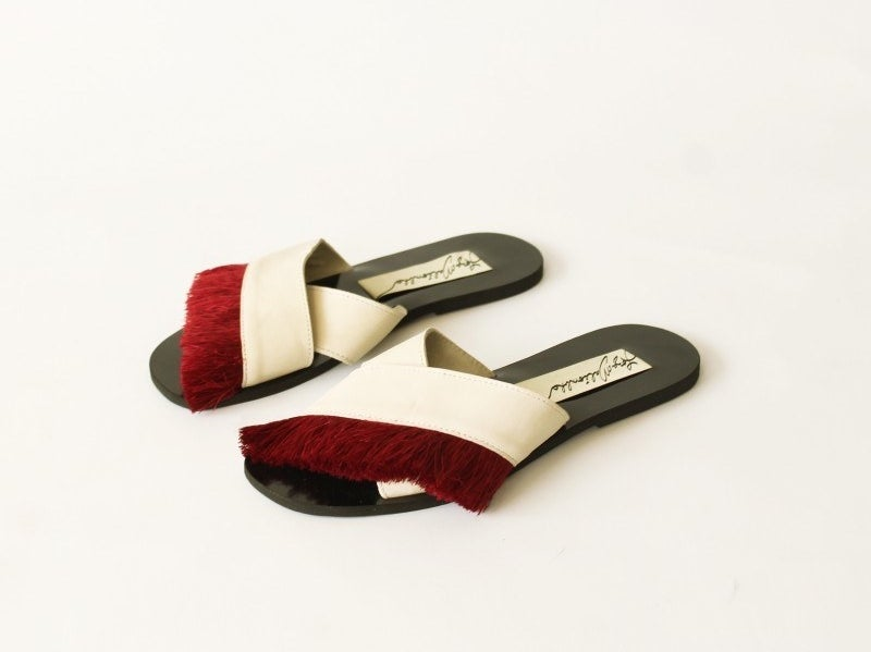 The slides with black sole and white crossed straps with one with red fringe across the top