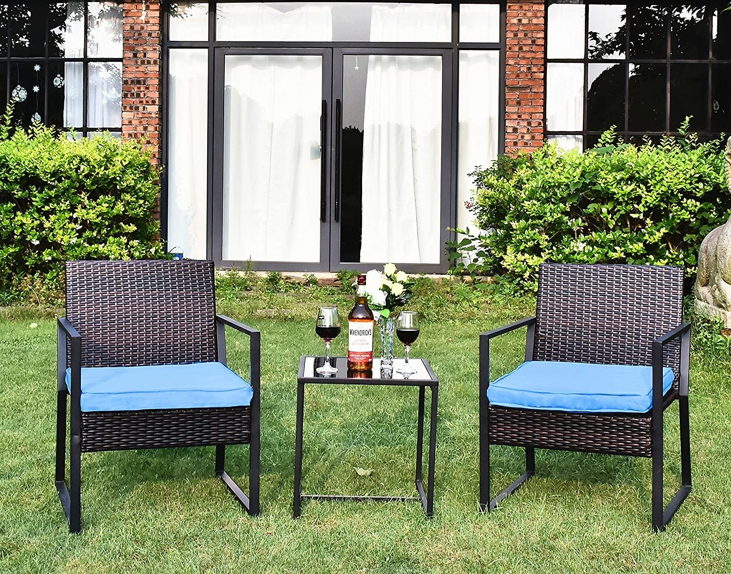two basket woven look arm chairs with blue cushions and a side table with a glass top in a yard