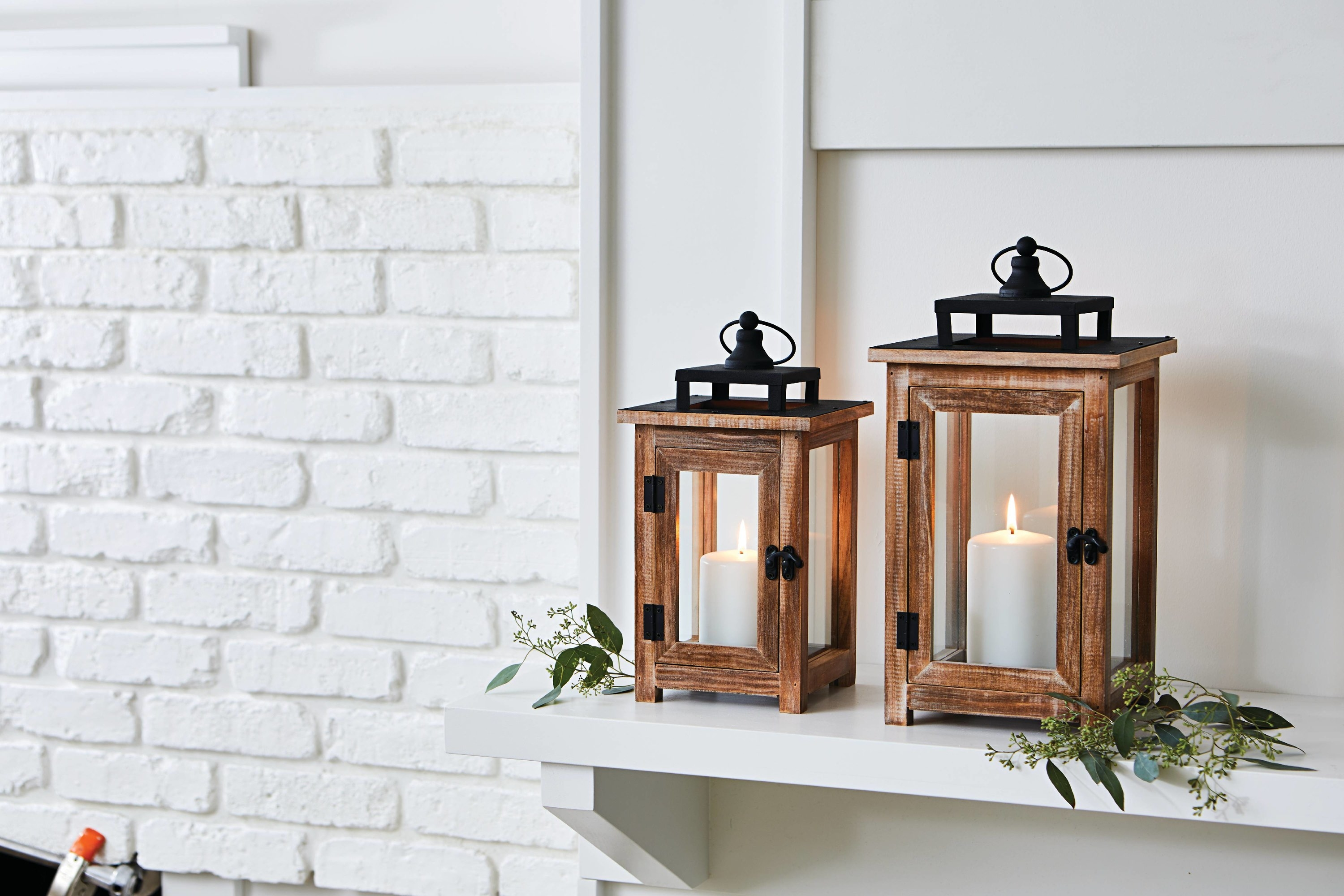 Two wood lanterns with glass windows in two sizes on a mantel