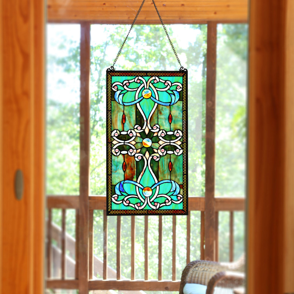 A rectangular stained glass panel hanging on a window