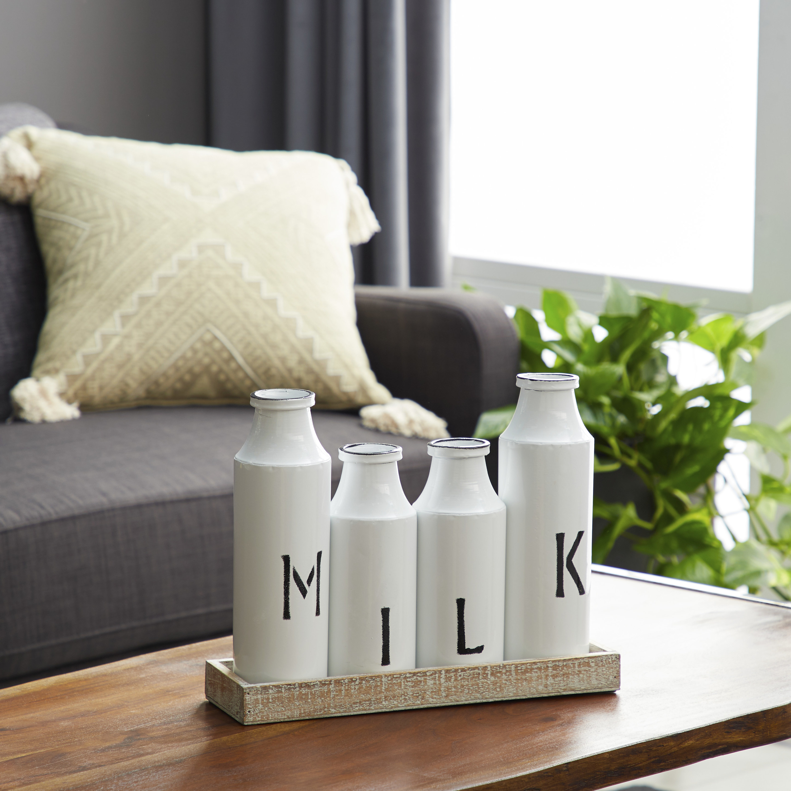 """Four white bottles that spell out """"Milk"""" in black text"""
