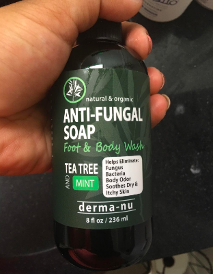 A reviewer holding up the pump-bottle of soap