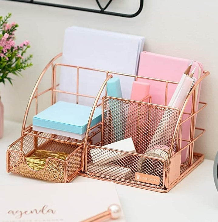 A rose gold desk organizer filled with pens, notes, paper clips, tape, and more