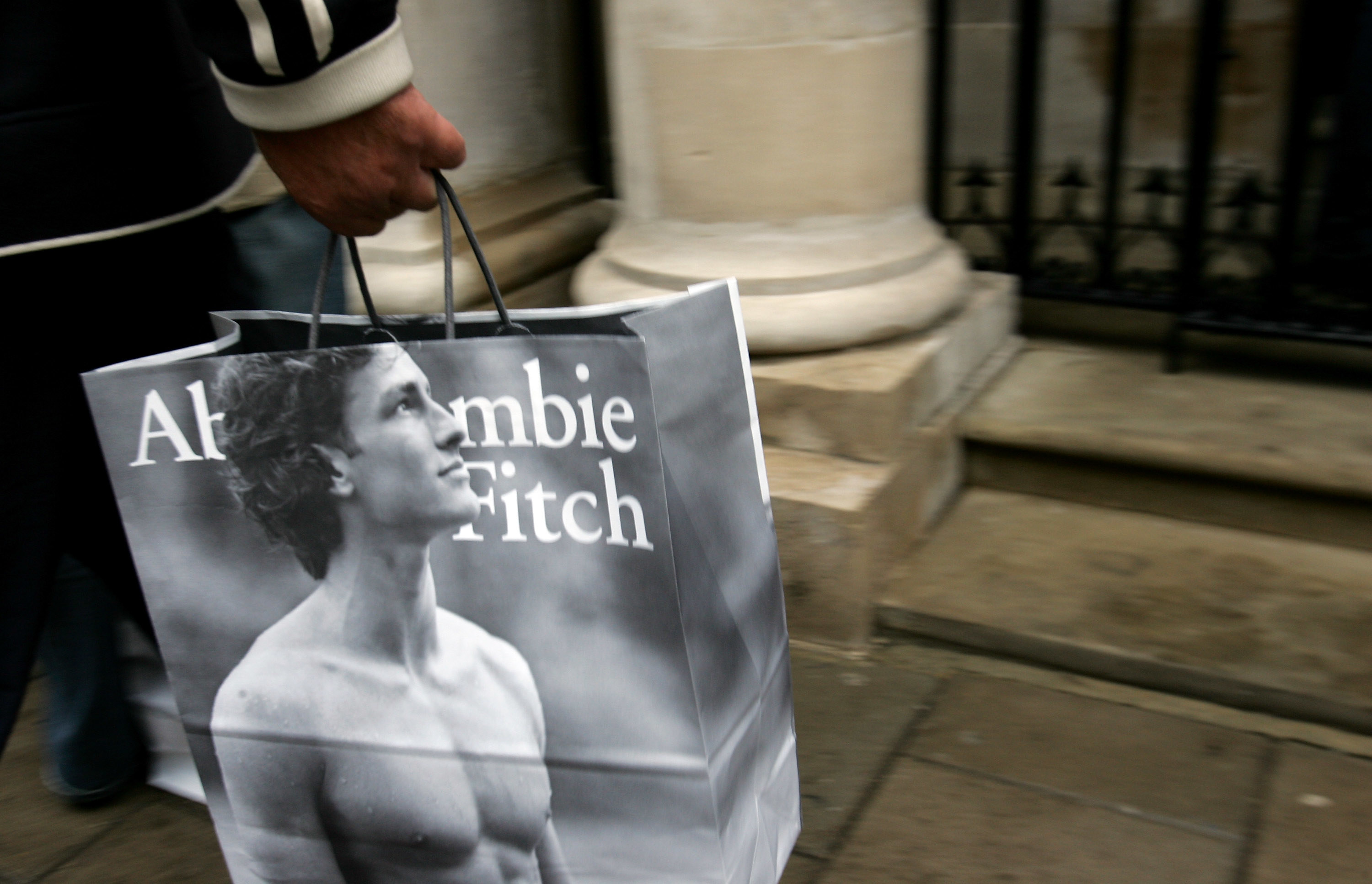 A close-up of a man carrying a black and white Abercrombie & Fitch bag with a shirtless model on it.
