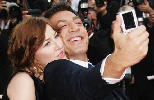 Photo of Kelly Macdonald looking over Javier Bardem's shoulder as he takes a selfie of the two of them with a digital camera.