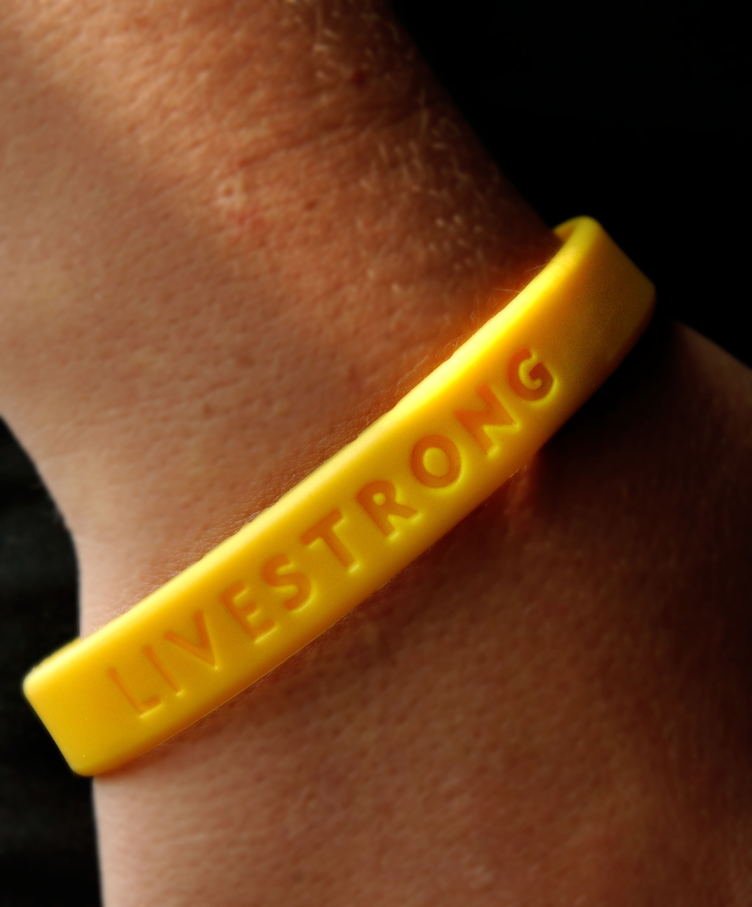 Close-up of a yellow LiveStrong bracelet being worn by someone.
