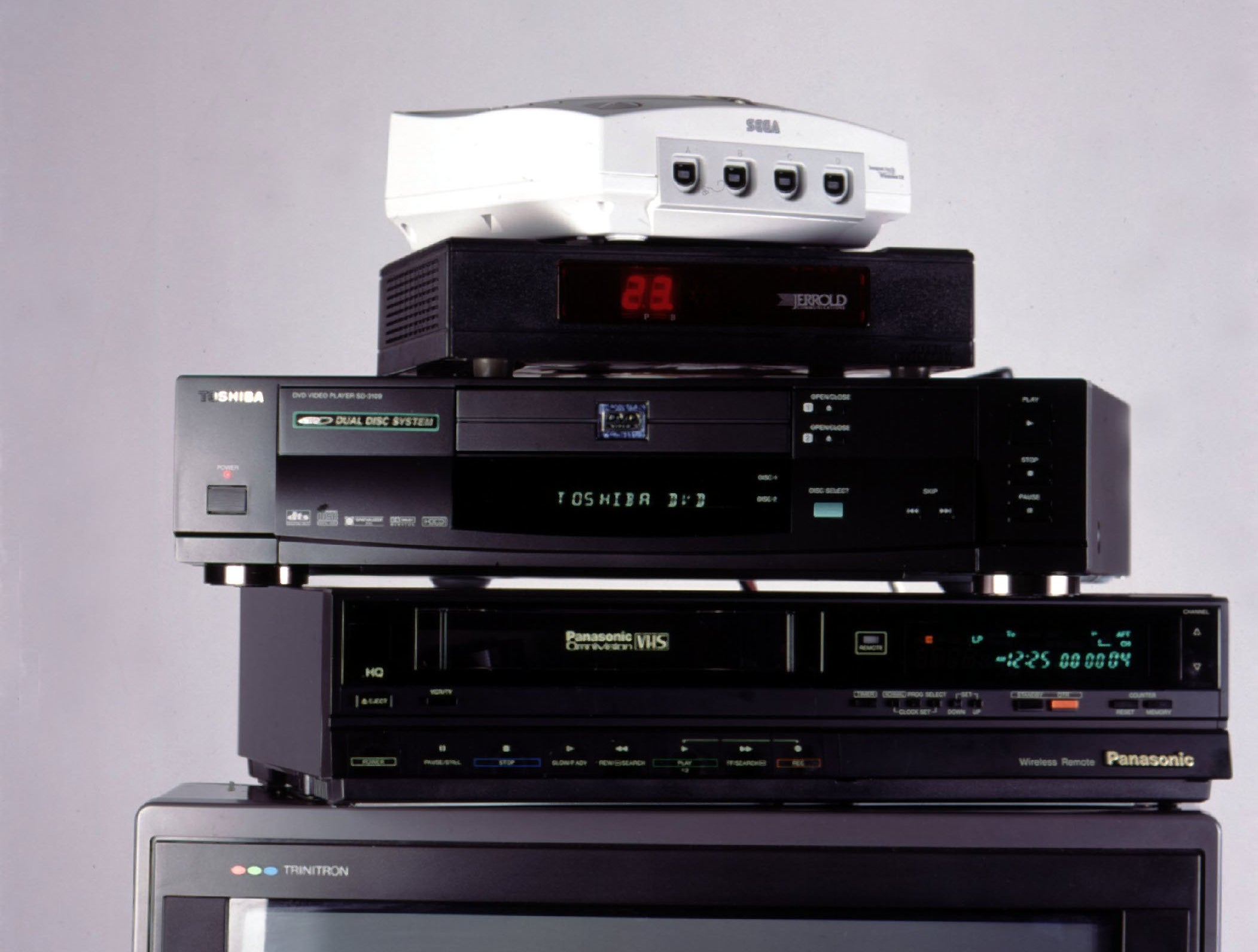 A Sega DreamCast, a DVD player, and a VCR stacked on top of TV.