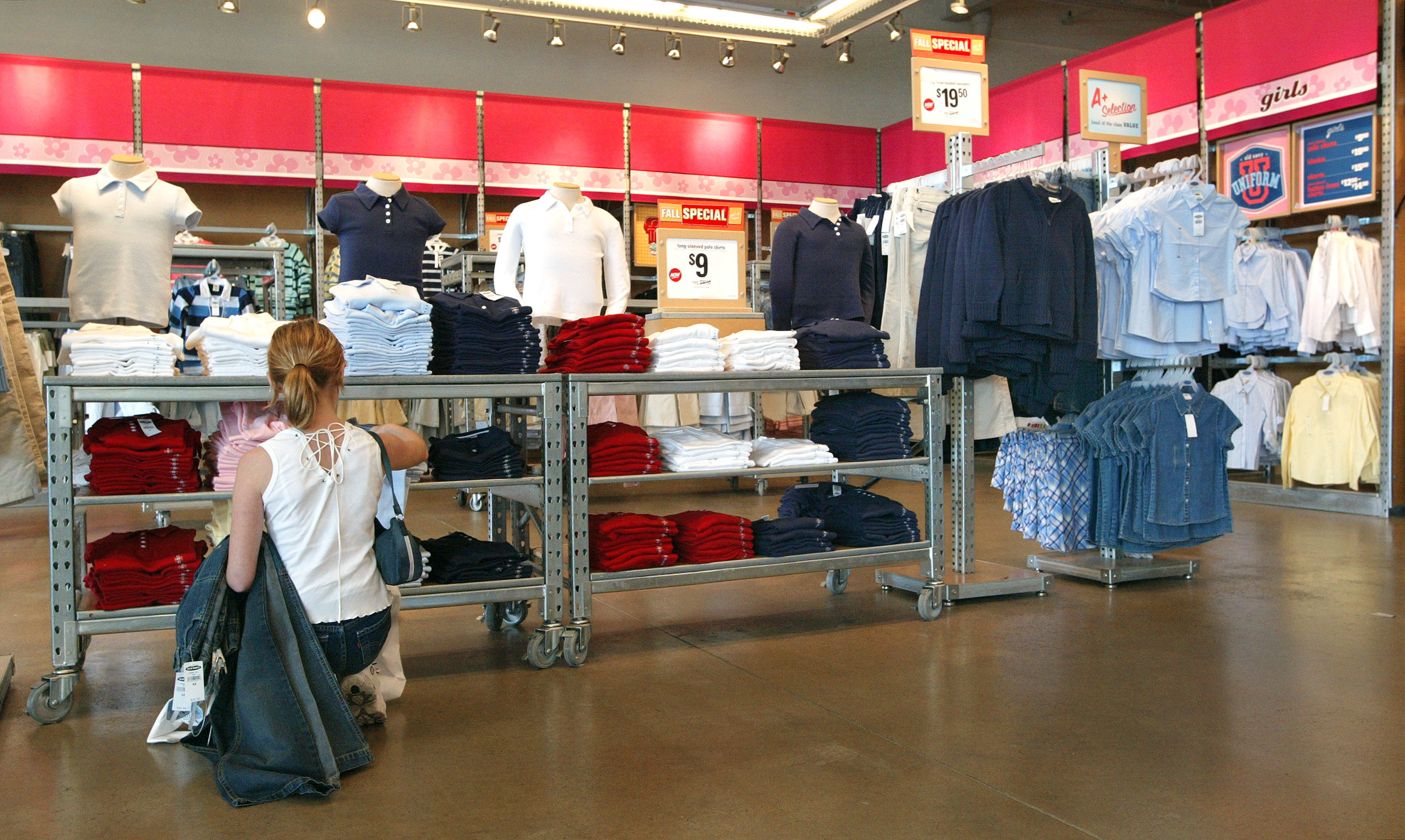 Woman holding several pairs of jeans, while crouched inside of a Old Navy looking at button up polos for girls.