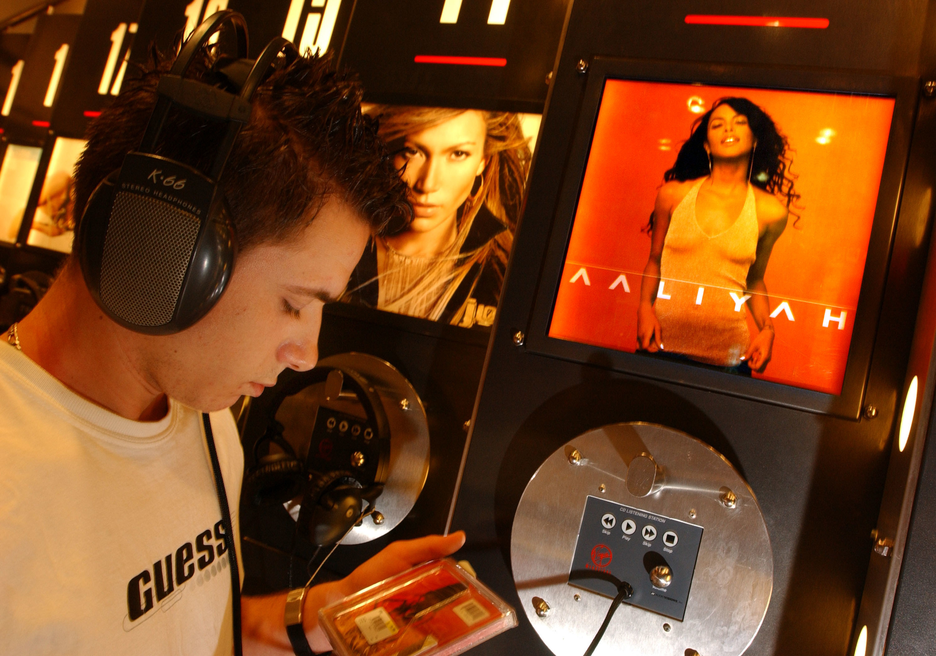 A man listening to Aaliyah's Aaliyah album at a CD kiosk inside a Virgin Megastore.