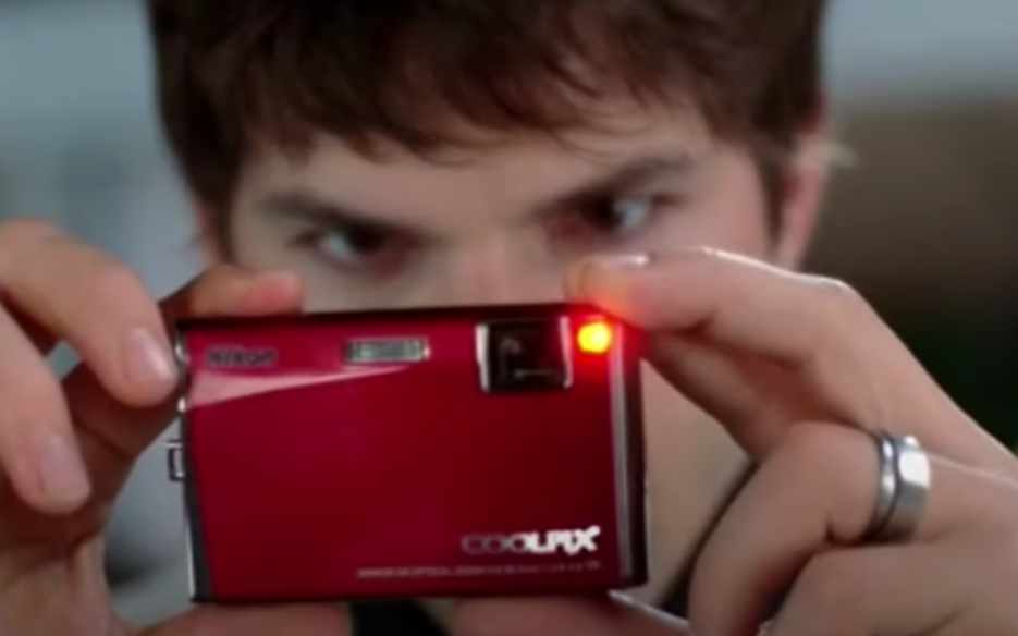 A photo of Ashton Kutcher taking a photo of with a red Nikon CoolPix camera.