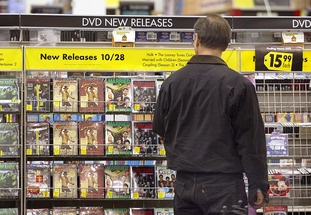 A man looking at newly released DVDs inside of Best Buy.