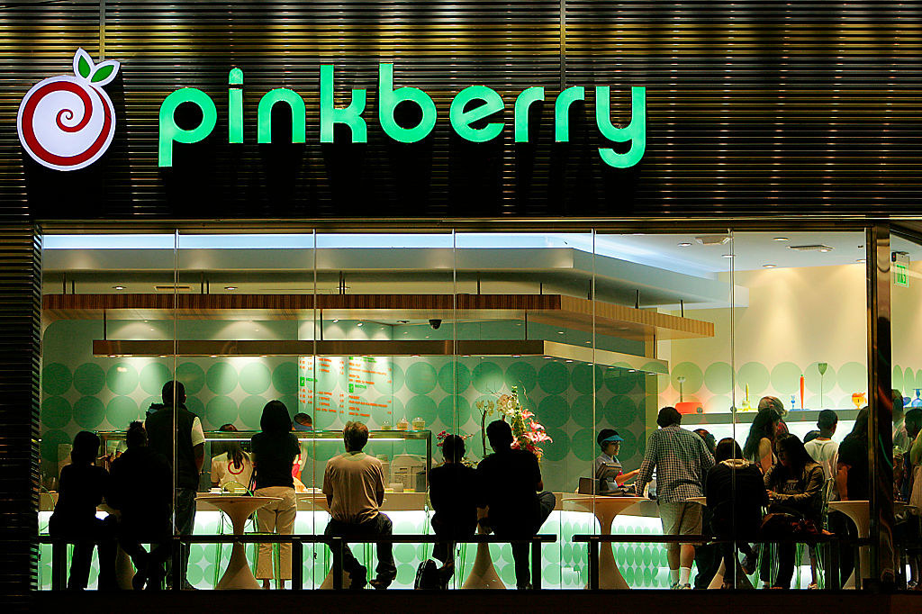 External photo of a crowded Pink Berry's at night with large windows and people sitting down enjoying their frozen yogurt.