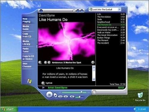 A Windows Media Player with hot pink swirl as the visualization and with a sunny hilly  wallpaper behind the player.