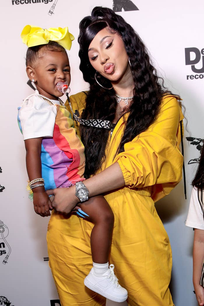 Cardi B puckers her lips to make a kissy face pose while holding her daughter