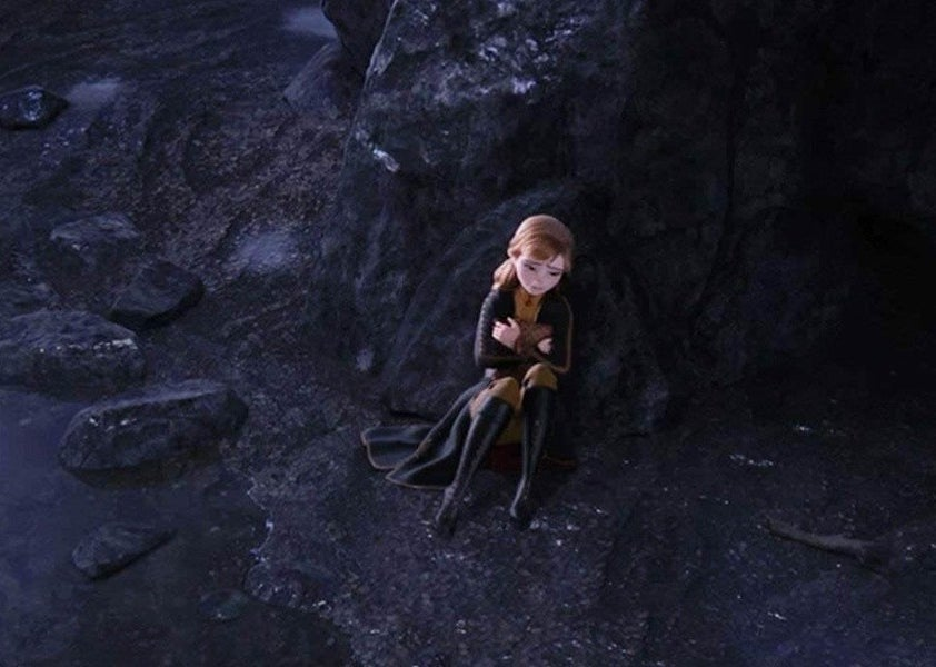Anna sitting alone in a cave crying