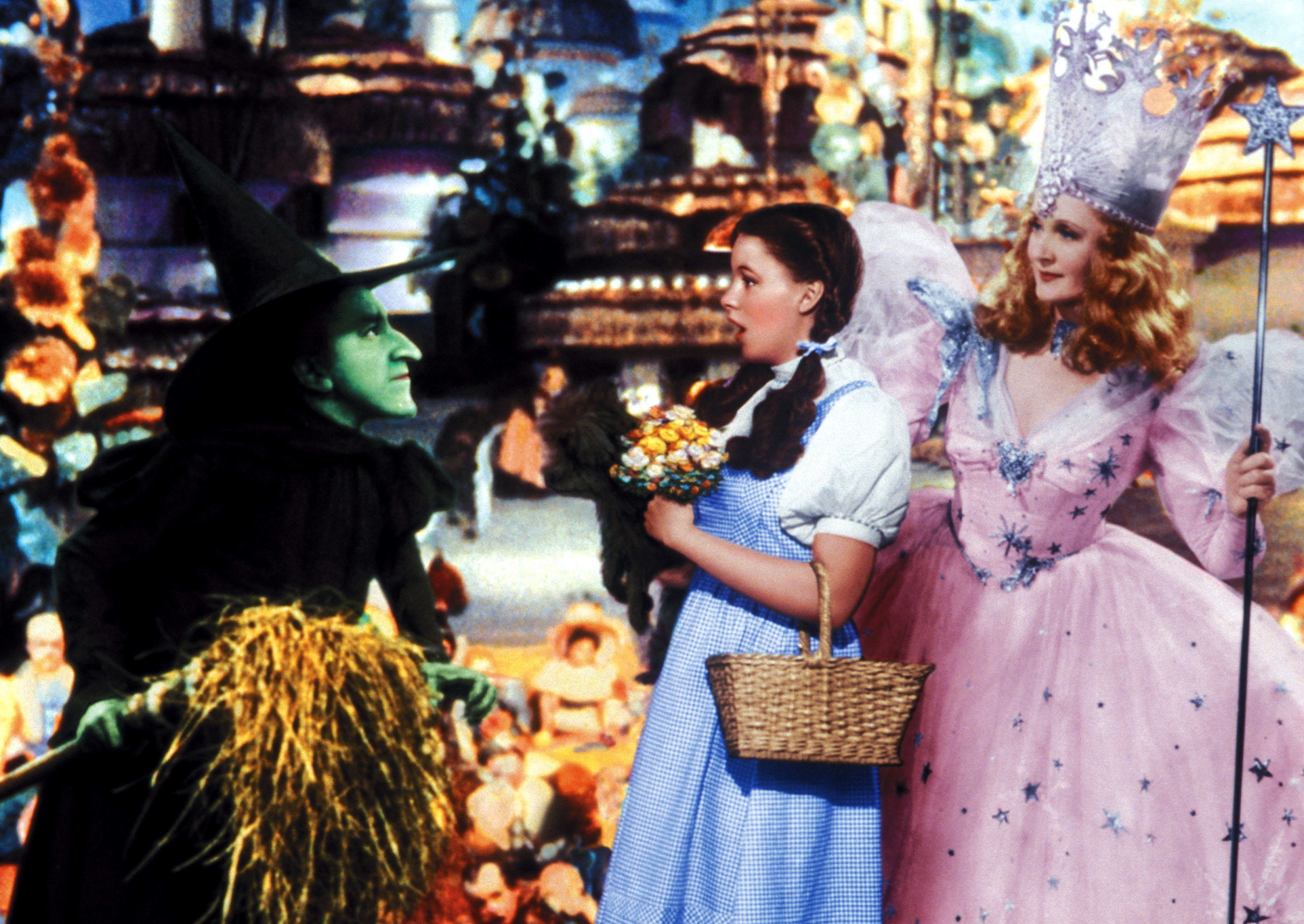 Dorothy standing scared between Glinda the Good Witch and the Wicked Witch of the West