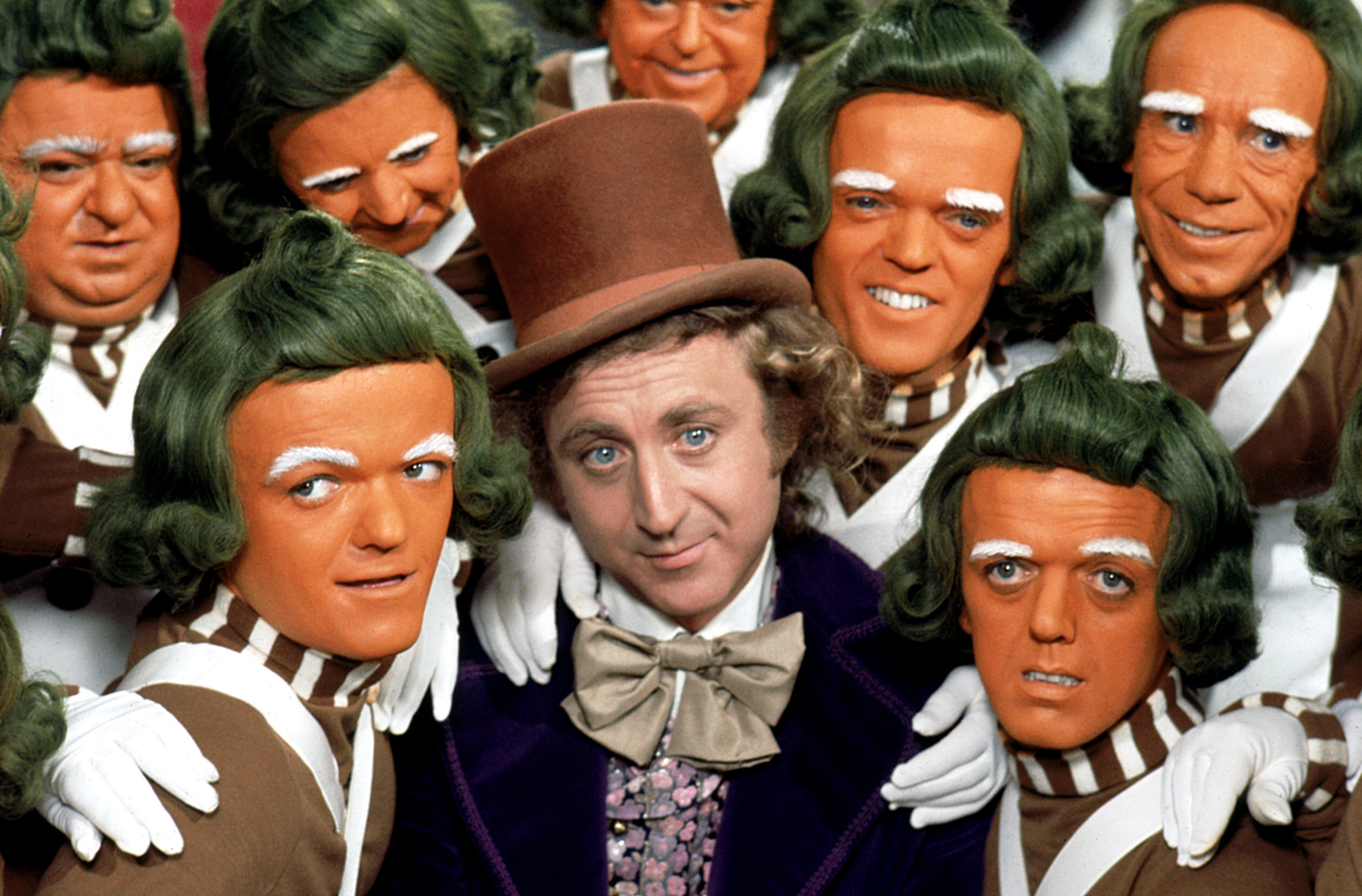 Willy Wonka surrounded by Oompa Loompas