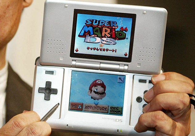 Close-up of an open Nintendo DS with the Super Mario 64 DS game home screen being on the game system's two screens.