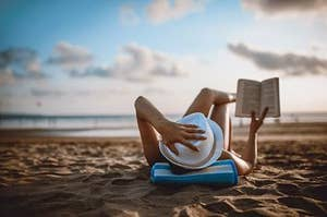 Person reading a book on the beach