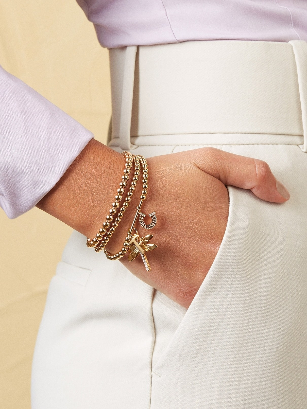 model wearing layered gold bracelet with charms