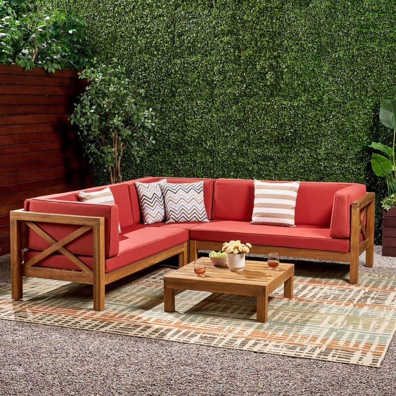 a four piece outdoor sectional with red cushions