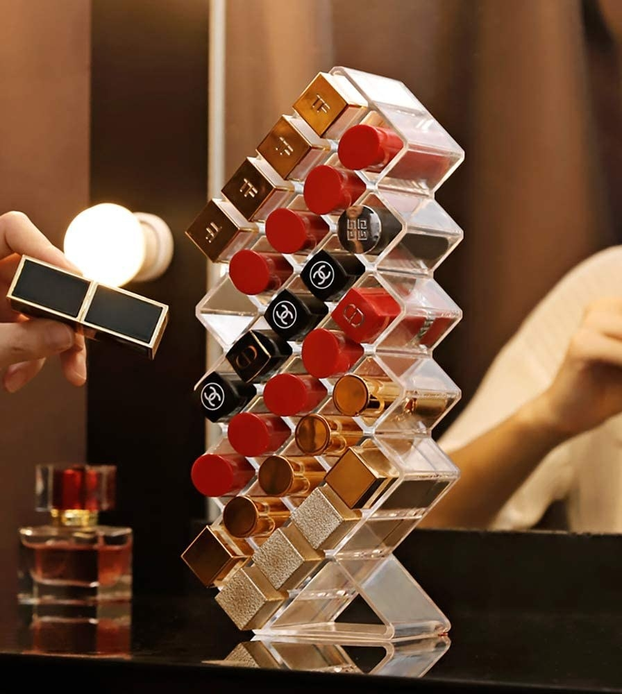 A person adding a lipstick to an almost-full acrylic lipstick holder