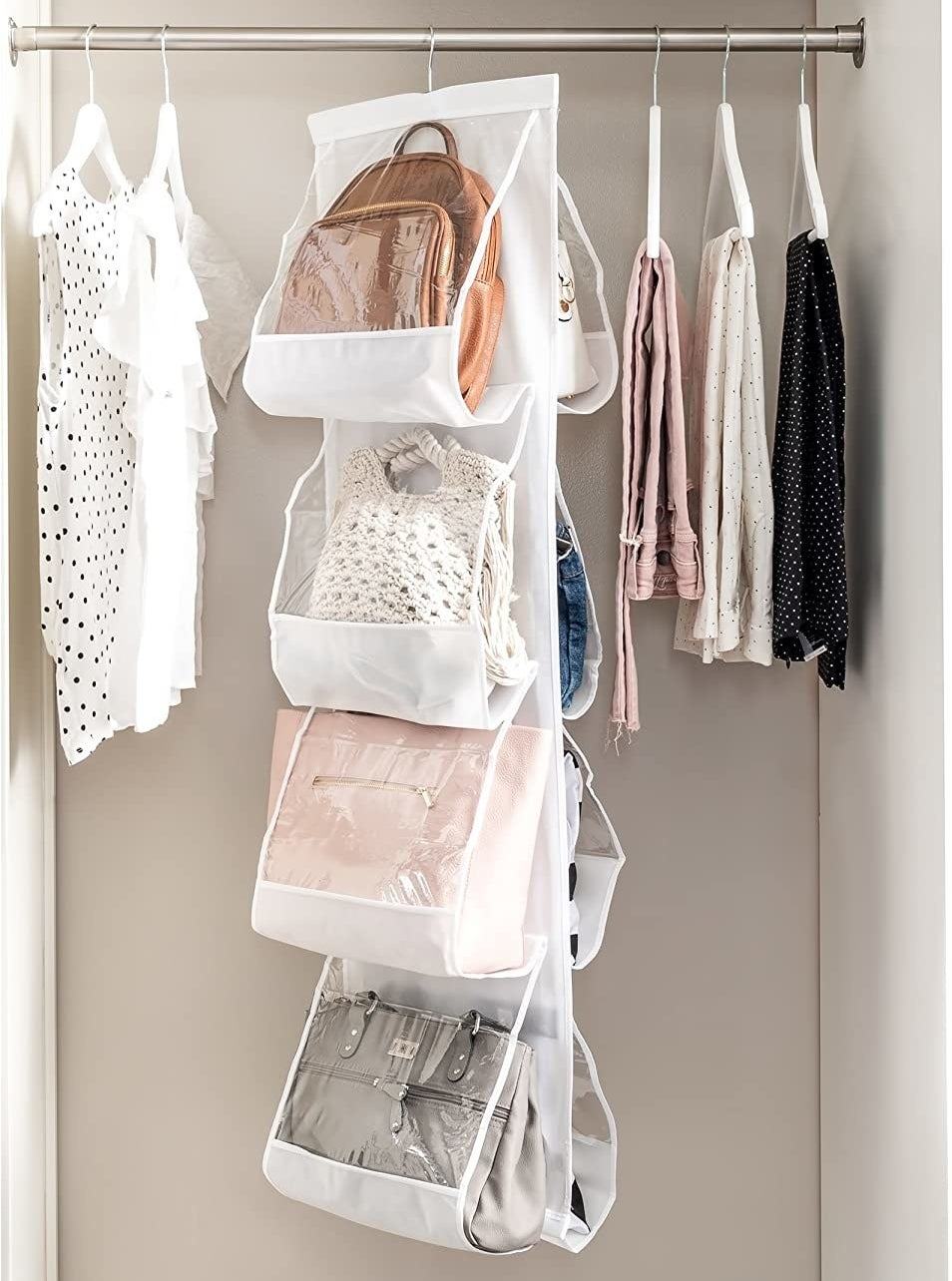 Eight handbags inside the handbag organizer in a closet