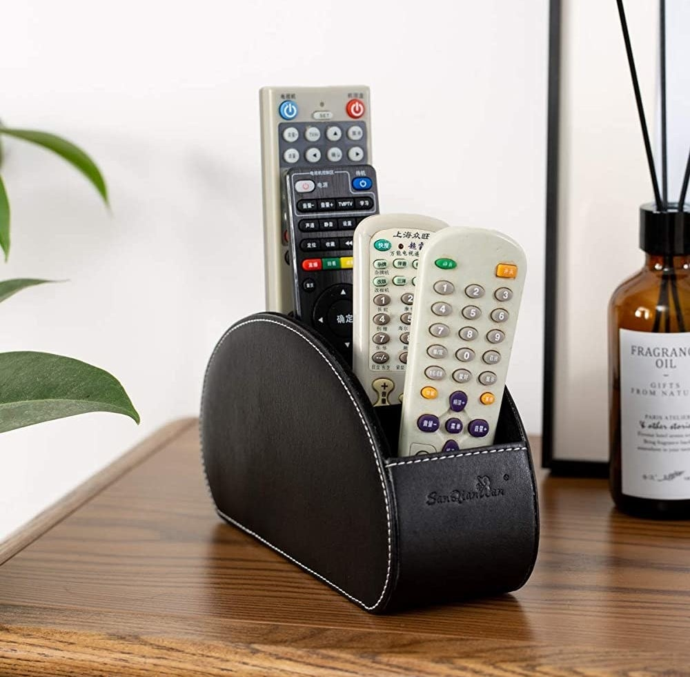 Four remotes in the remote control holder on a table