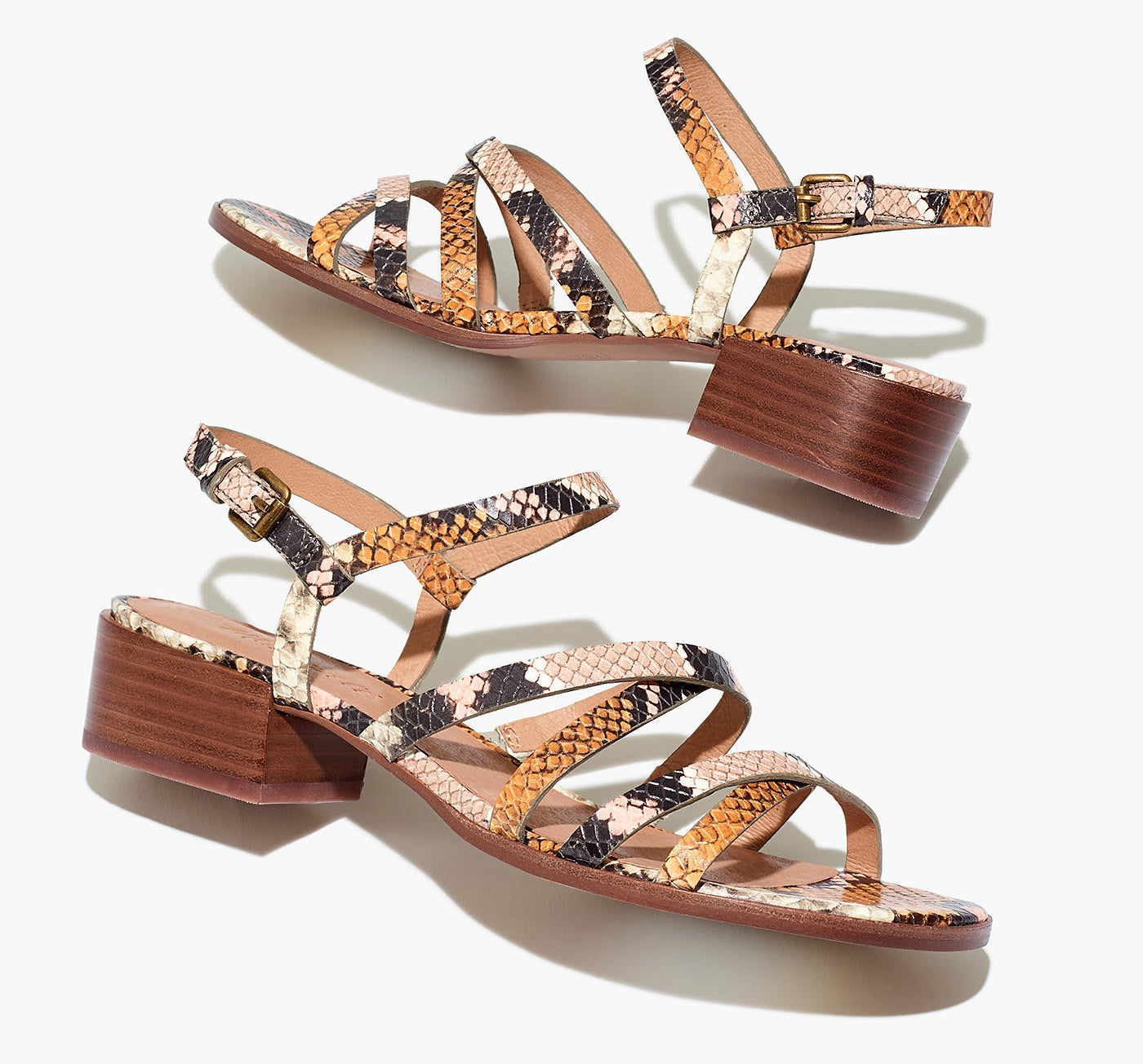 Strappy sandals with a small chunky heel and buckle back in a black, white, pink, and orange snakeskin print