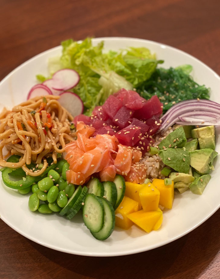 A poke bowl with diced tuna, salmon, sesame noodles, and lots of chopped vegetables over rice and lettuce.