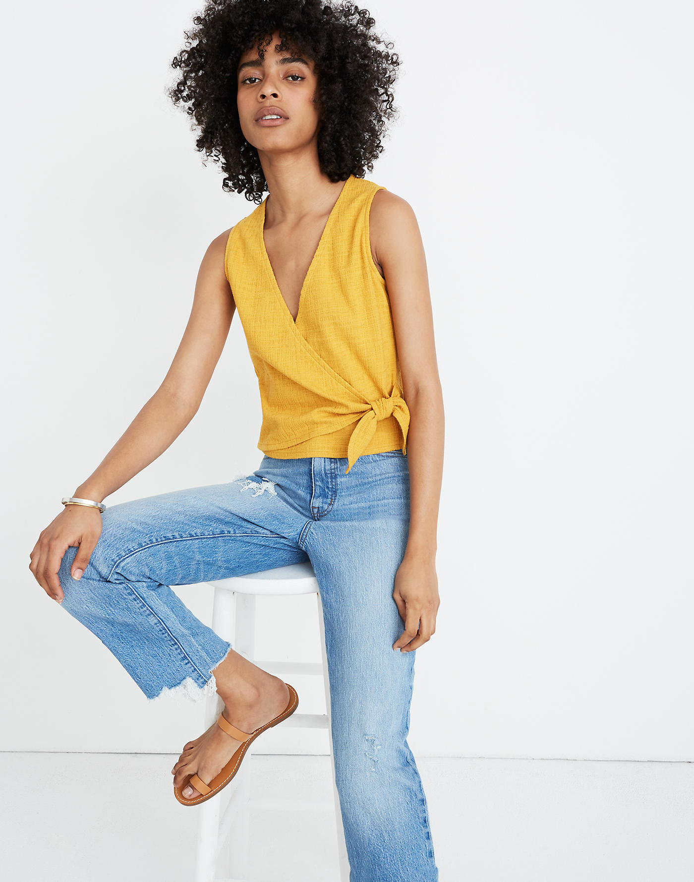 Model wearing the v-neck tank with a wrap around the front in yellow