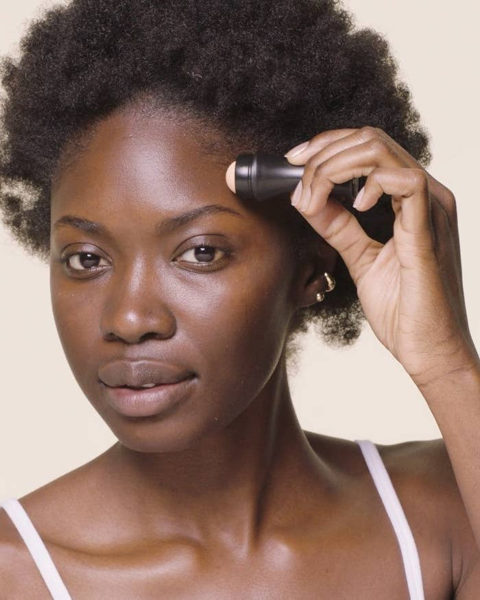 A person rolls the facial roller over their face, leaving it looking smooth and oil-free