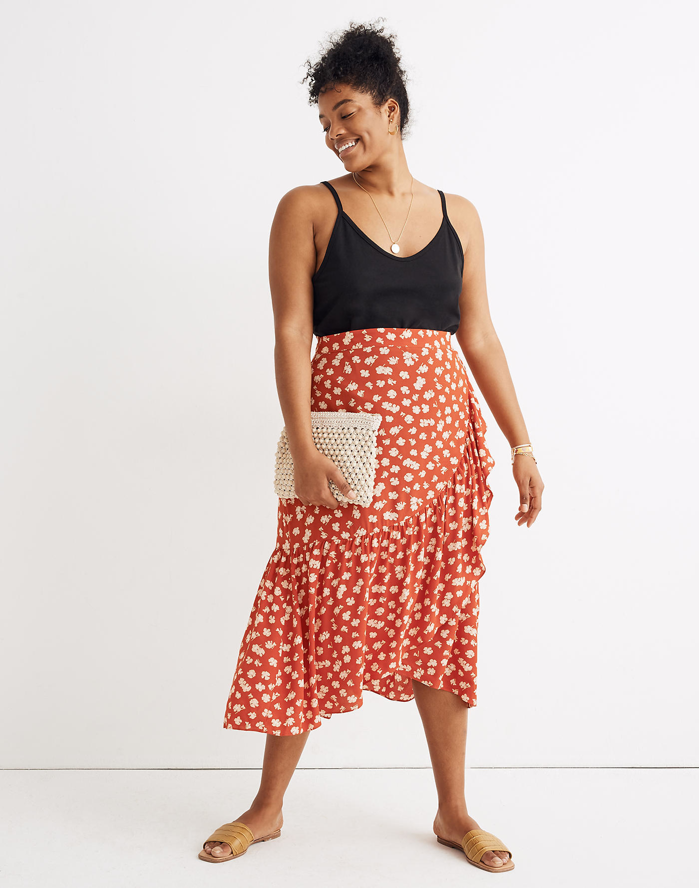 Model wearing the wrap skirt with a wide ruffle across the bottom edge in orange with small white flowers on it