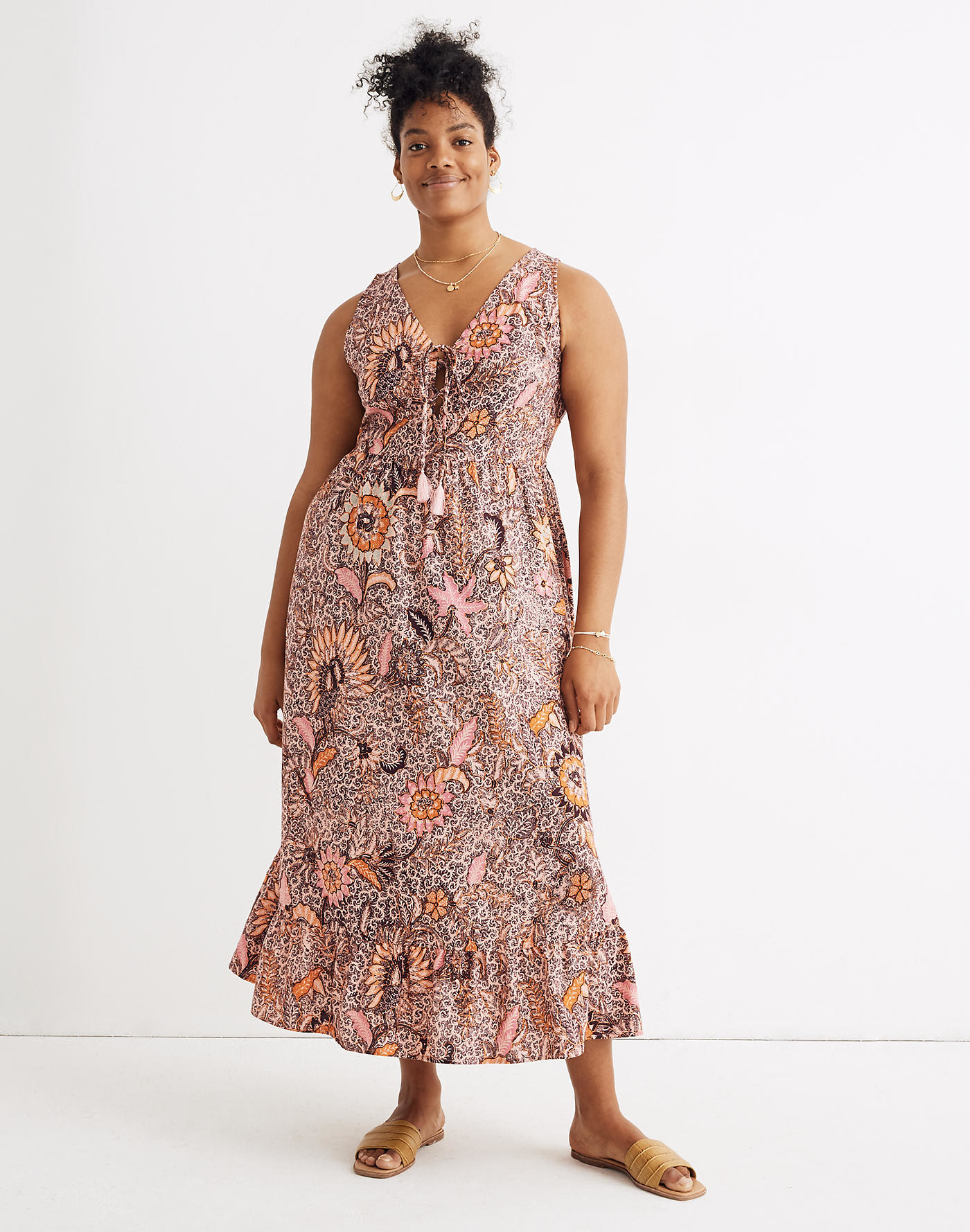 Model wearing dress with a ruffle along the bottom hem, tie in the middle of the v-neck and pink, orange, and brown floral graphic pattern