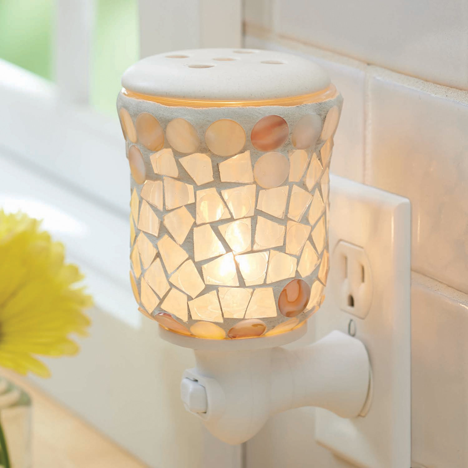 A ceramic patterned warmer plugged into the wall