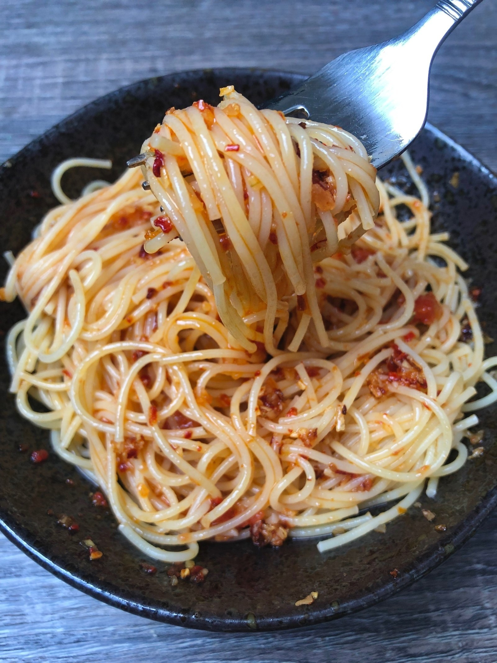 A bowl of spaghetti with chili onion crunch condiment.