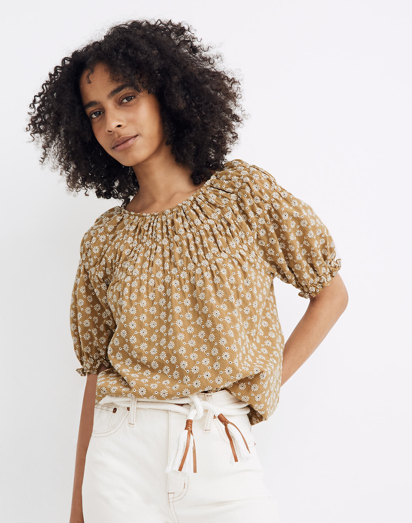 Model wearing the puff-sleeve top with elastic around the short sleeves and a daisy embroidered pattern all over