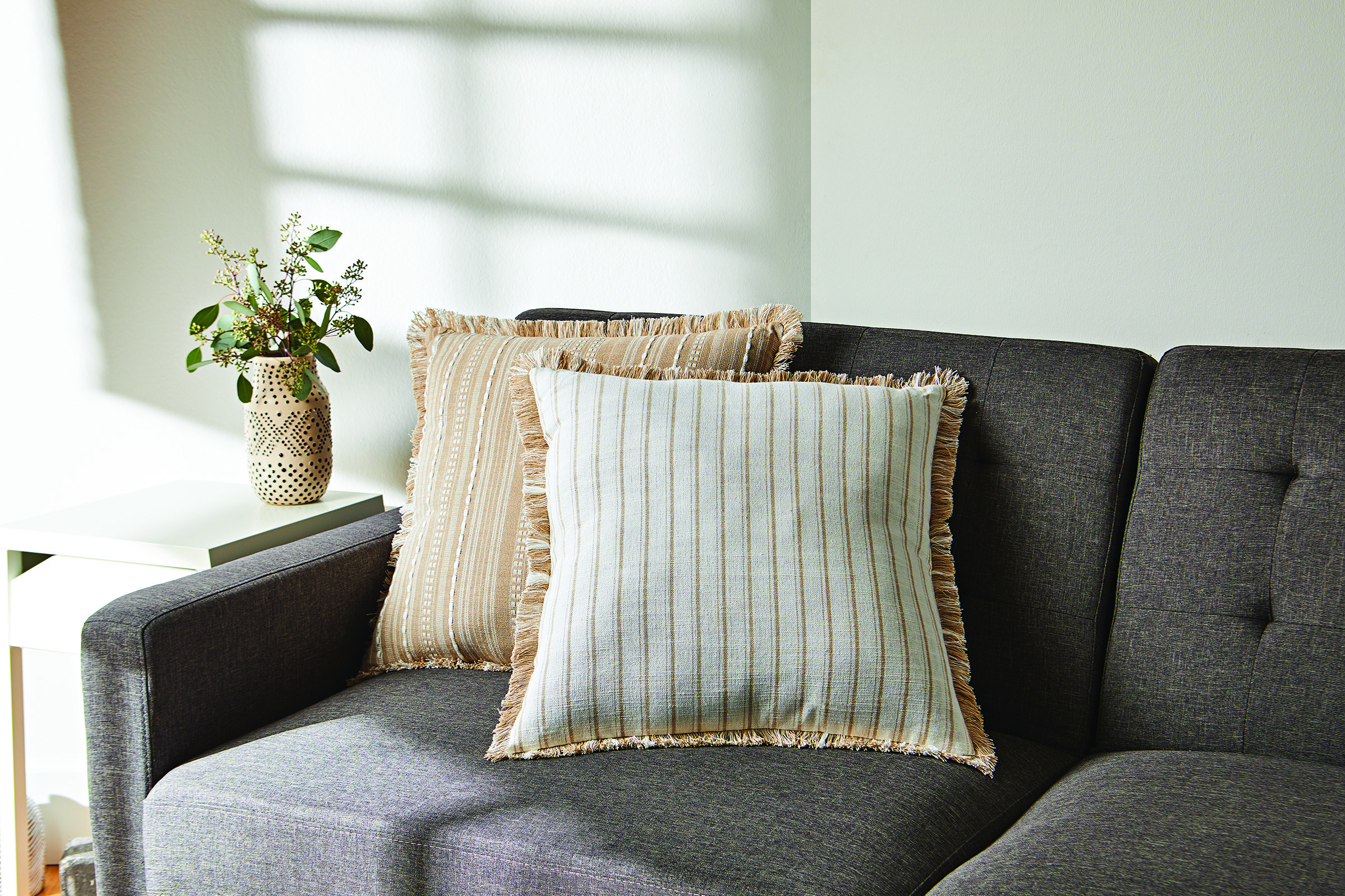 white and gold reversible striped pillow with fringe accents