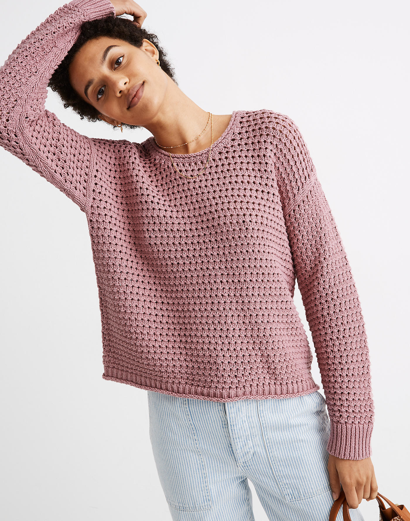 Model wearing the sweater with a rolled neck and hem in pink