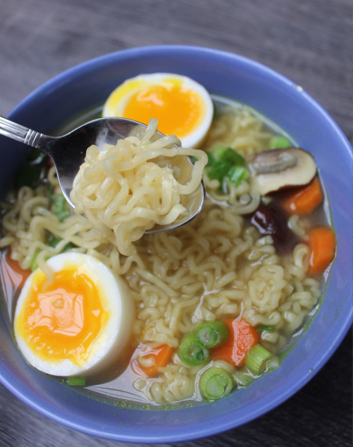 A spoon taking a bite of insant ramen soup with a soft boiled egg, carrots, mushroom, and scallion.