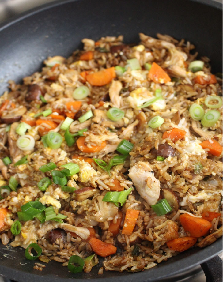 A skillet full of fried rice with chicken, vegetables, and scallions.