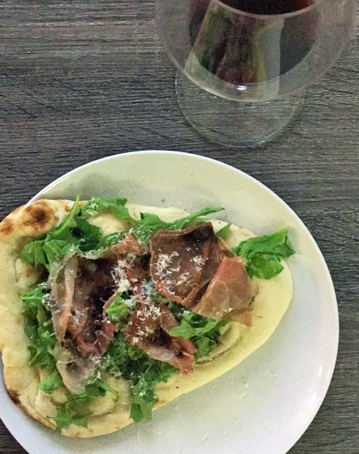 A piece of naan topped with prosciutto, arugula, and parmesan cheese.