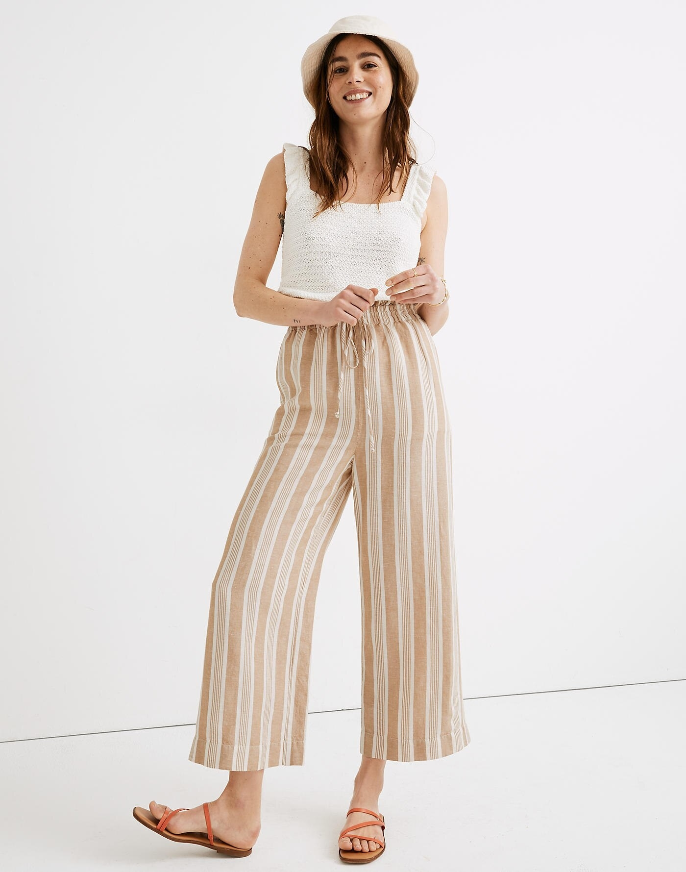 Model wearing the pants with a smocked waist and tan and white vertical stripes