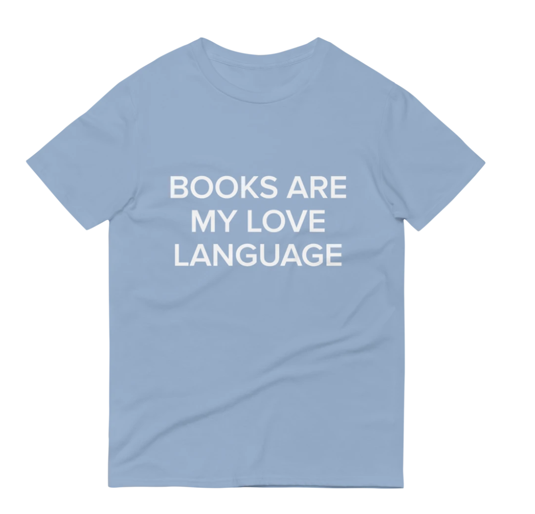 "A blue shirt that says ""Books Are My Love Language"" in white"